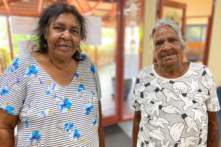 Two Indigenous women wearing patterned shirts stand together inside.