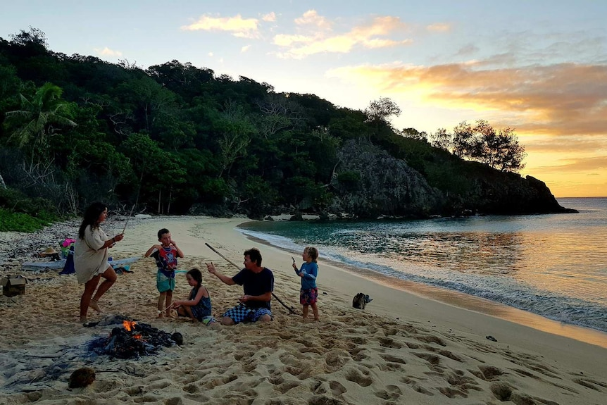 a family sit on a beach next to campfire with a sunset and jungle in the background