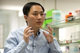 He Jiankui gestures with his hands while speaking during an interview.
