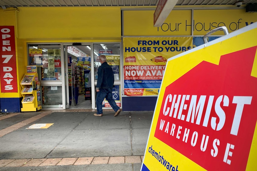 A man walks into a bright yellow Chemist Warehouse store.