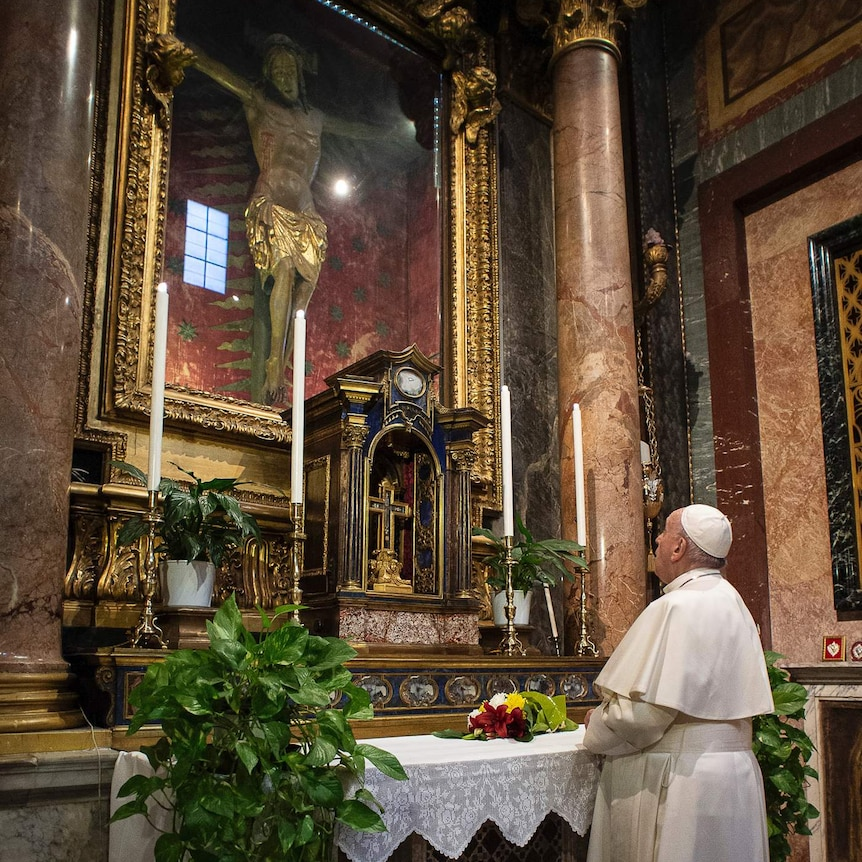 Pope Francis prays in front of a statue of Jesus on a cross that is housed behind glass.