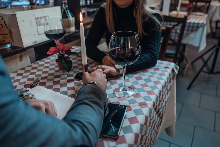 Couple holding hands over a candlelit dinner