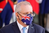 Morrison wearing an Australian flag print face mask with a headphone in his ear