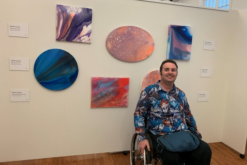 a man smiles at the camera in front of several pieces of colourful abstract art