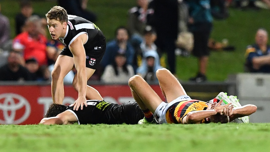 Two players laying on the ground after they collided during an afl match