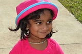 A tight mid-shot of a young Tamil girl wearing a pink shirt and pink and blue hat.