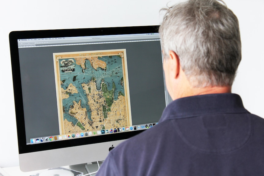 Tony Sheffield sits at his desk editing a map of Sydney on computer.