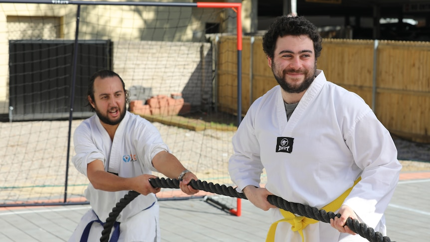 Two men with smiling faces wearing white martial arts uniforms and pulling a rope in a game of tug-o-war.