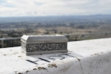 An ornate box sits on a cement barrier overlooking the Bathurst plains. HDT (Holden Dealer Team) is painted on the barrier