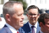 Butler wearing dark-rimmed glasses watches an out of focus Shorten speak to the media.