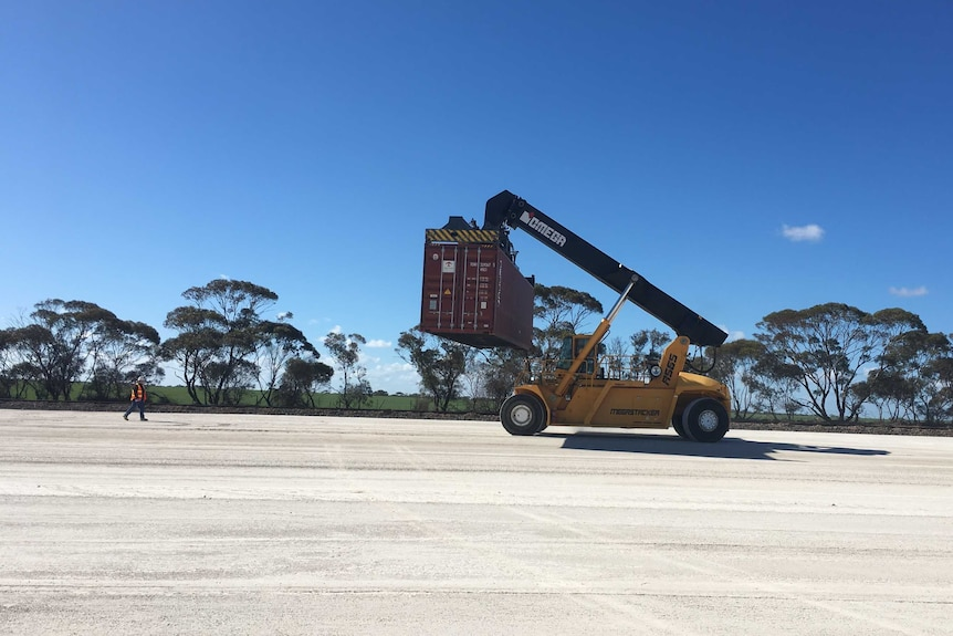 A shipping container is picked up at a loading pad.