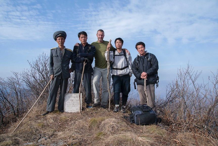 Roger Shepherd poses with four Asian men on top of a mountain.