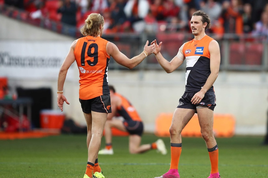 Two defenders clasp hands in celebration at the end of an AFL game in Sydney.