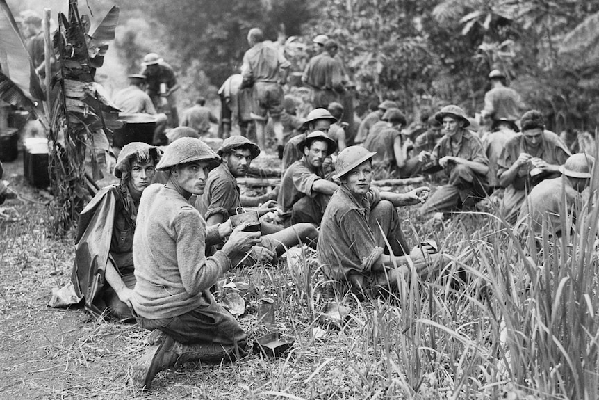 Men in a jungle setting eating food