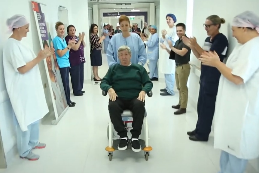 A man in a wheelchair is pushed through a corridor which doctors and nurses have lined