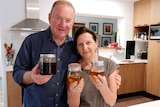 Graeme Connors with his wife Lyn, holding jars of honey and smiling to the camera.