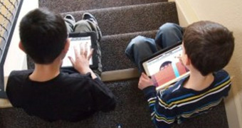 Children sit on steps with ipads.