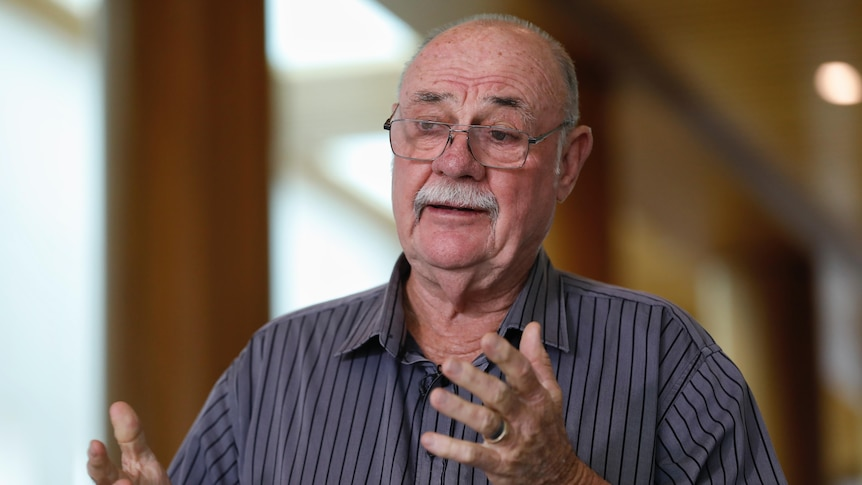 Warren Entsch holds out both arms while speaking inside.