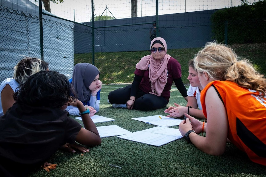 A woman sits on the grass with some junior football players, discussing strategy for the game.