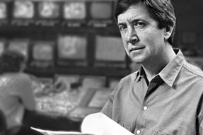 Black and white photo of Olle holding script with television monitors in background.