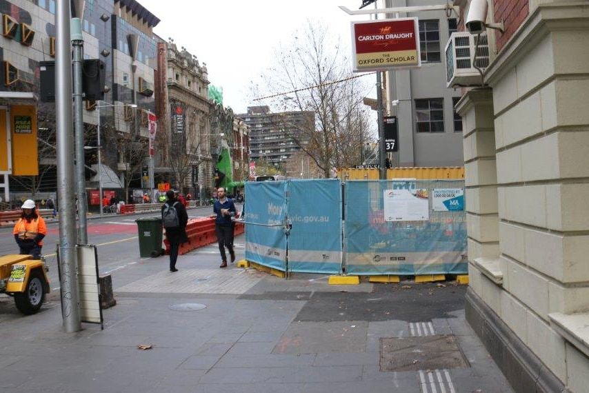 Construction barriers cover the footpath outside the Oxford Scholar hotel.