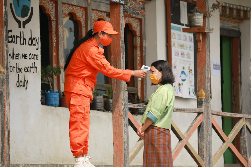 A woman dressed in orange pants and top and wearing orange mask and hat holds a thermometer to a woman's head.