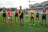 Eight football players wearing guernseys stand on an oval looking at the camera.