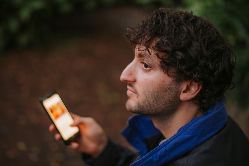 Over the shoulder shot of young man Alexi Barnstone on a dating app on his mobile phone.