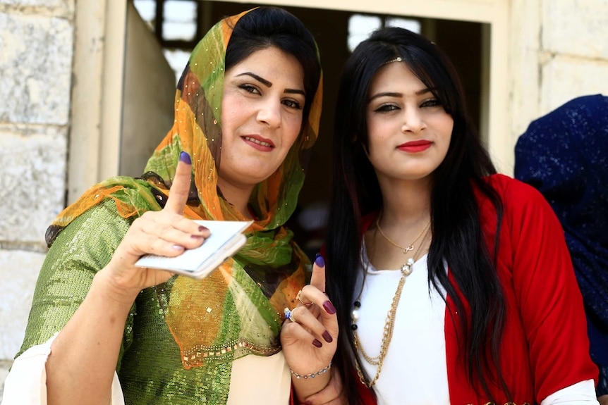 Kurdish women show their ink-stained fingers after voting.