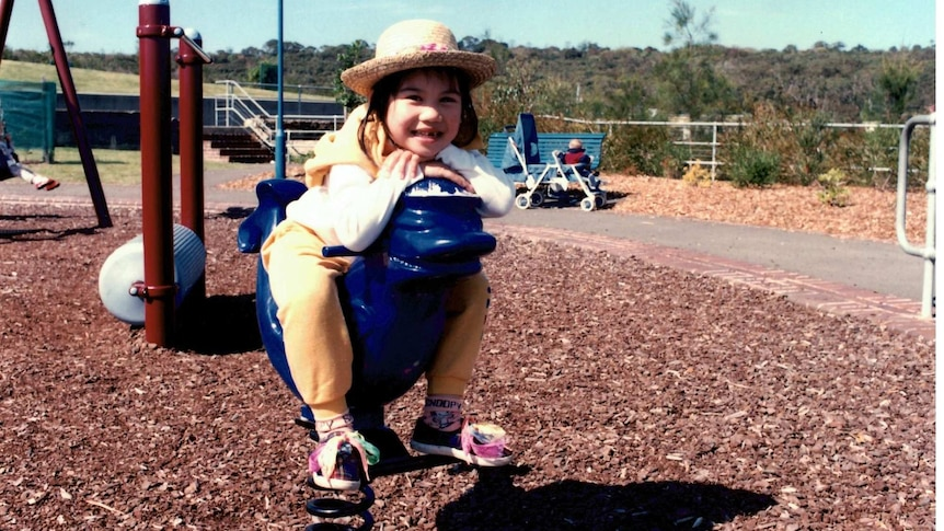 A girl smiles at the camera while sitting on playground equipment wearing a straw hat.