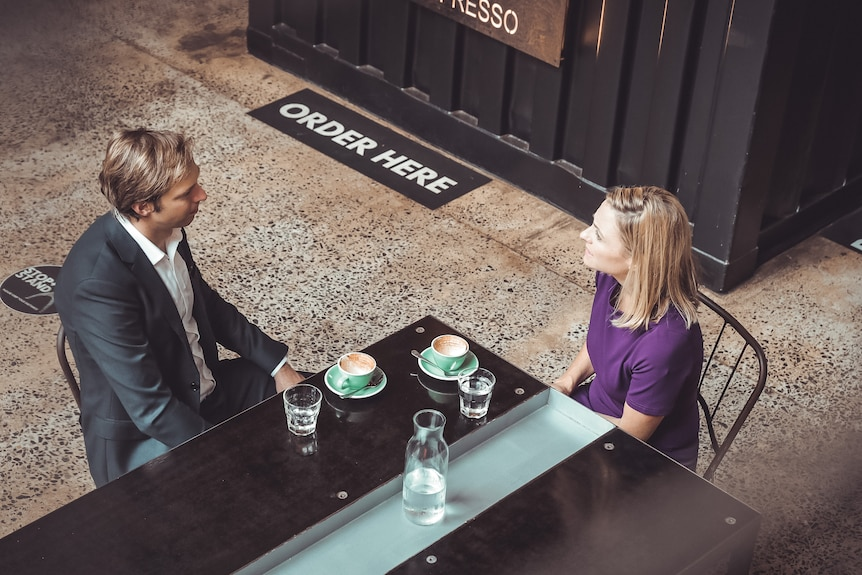 Man and woman have coffee at a cafe seen from above.