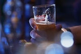 A man holds a beer in a bar