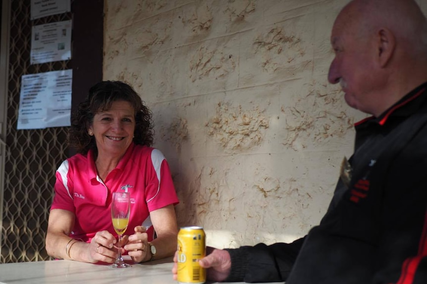 A middle aged lady with tight curly brown hair and a pink t shirt smiles at the camera while sitting at a table.