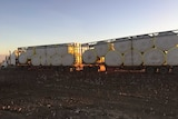 Road train loaded with cotton bales in desert-like area with sun setting in the background