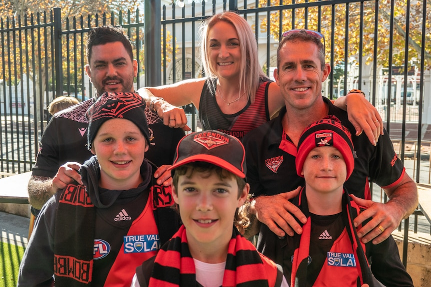 A family of Essendon fans stand in Bombers gear in front of a metal fence, with the kids in front and the mum and dad behind.