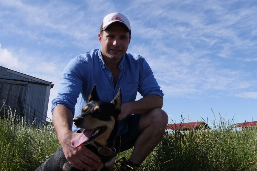 Man wearing a cap crouching behind a kelpie that's sitting down with sheds and a big blue sky behind them