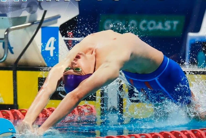 a boy dives out of the water in a backstroke position