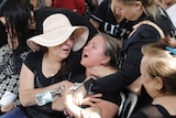 A woman wails as others try to carry her.