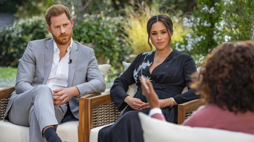 Prince Harry and Megan sit on armchairs, looking towards Oprah Winfrey, whose back is to the camera.