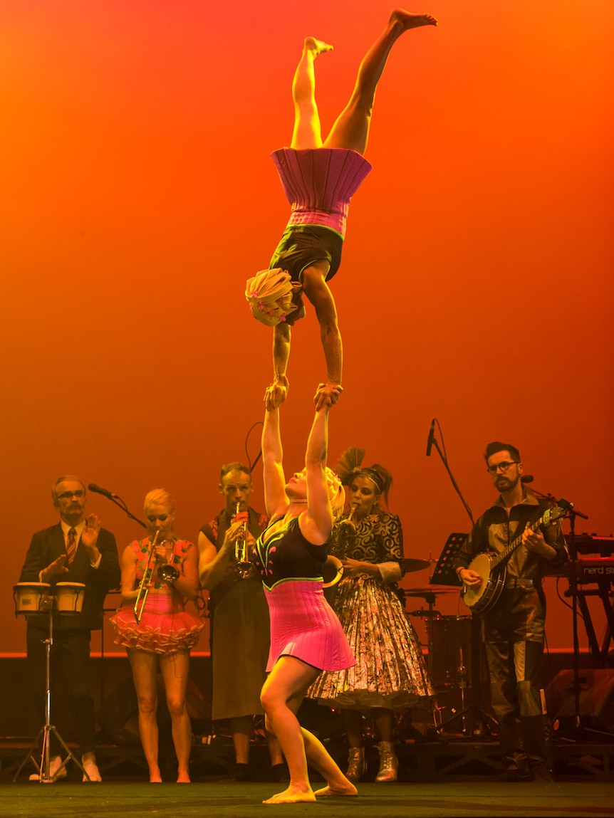 A woman holds another woman above her head, musicians in background.