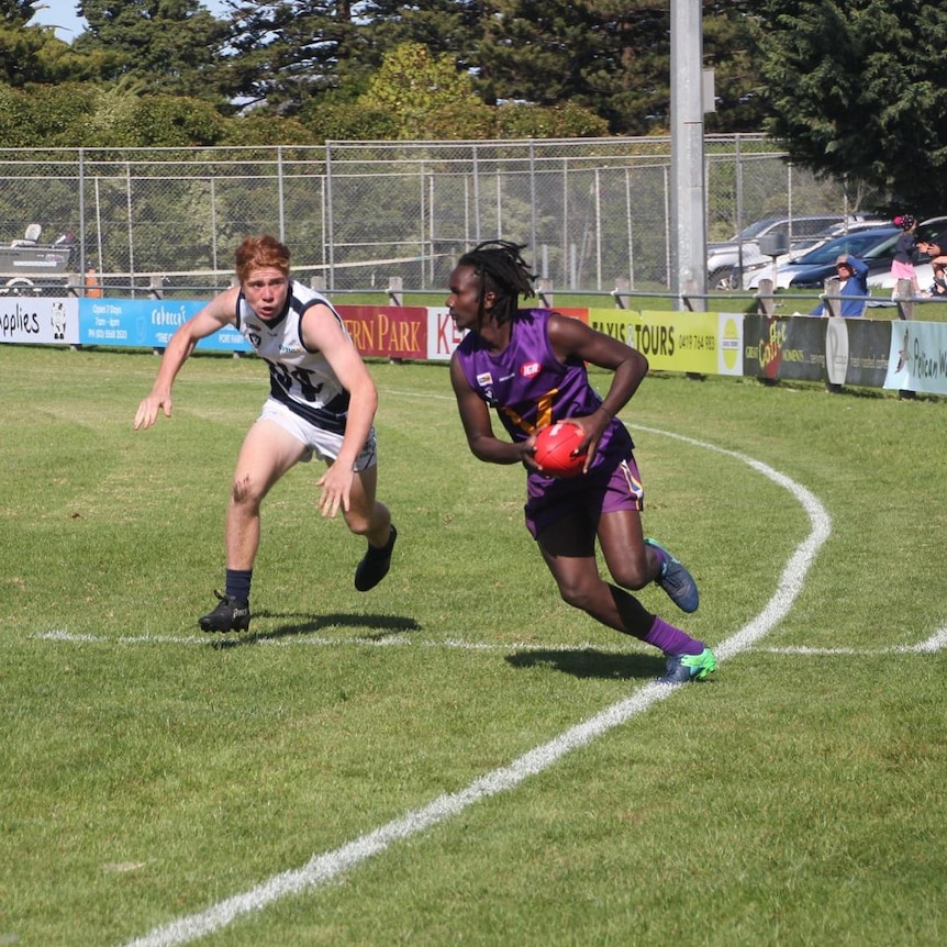 Two men play AFL football