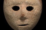 A close-up of a mask with a black background