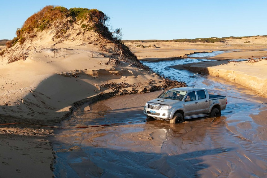 A four wheel drive attempting to winch another 4x4 out of sand in a shallow stream on a beach.