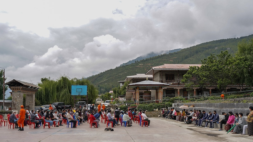 People line up outdoors in Thimpu to get their COVID vaccine on July 20, 2021.