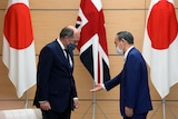 An Asian man gestures for a Caucasian man to sit down in a formal setting with flags of Japan and UK behind.