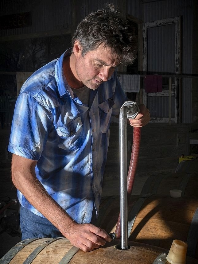 A man in a blue check shirt holds a pipe and hose placed in a hole in a wine barrel.