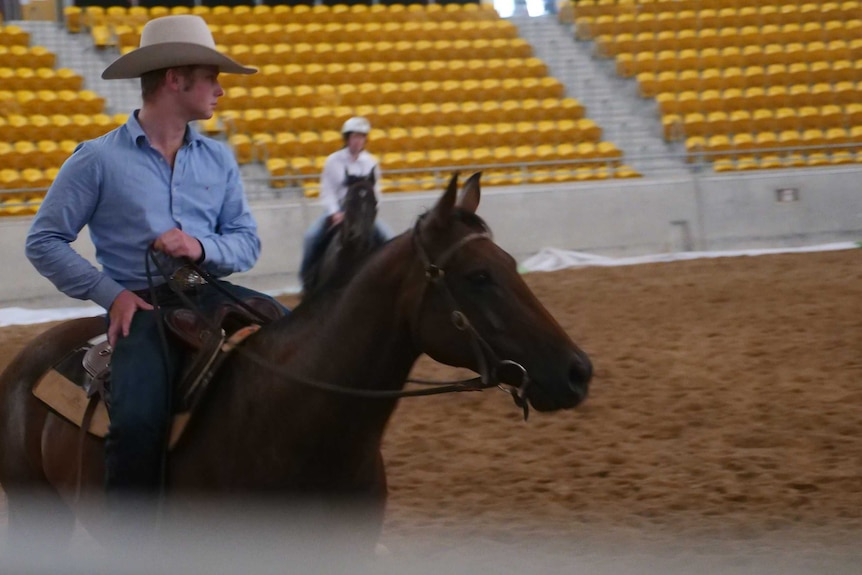 A man sits on his horse in an arena.