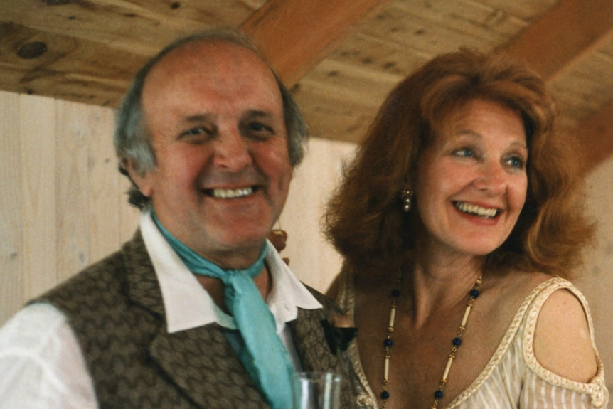A man and a woman on their wedding day, smiling holding a drink
