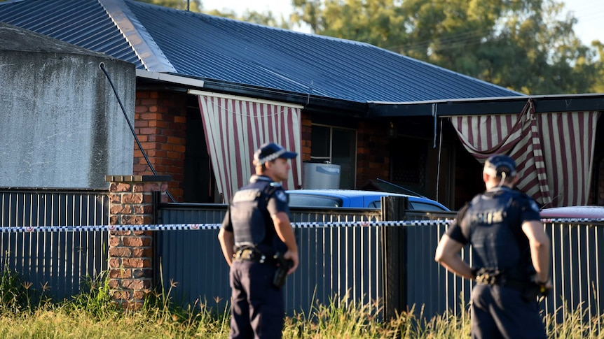 Police guard a house.