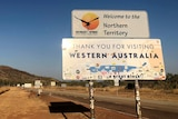 """A sign says """"Welcome to the Northern Territory"""" and """"Thank you for visiting Western Australia""""."""